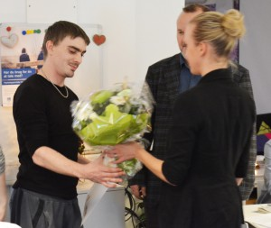 Tino overrækkes blomster og bevis